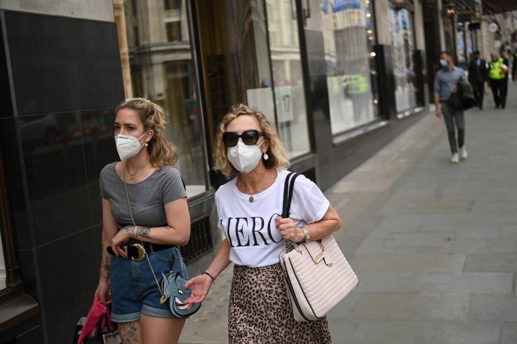 شابتان تتنزهان في لندن مرتديتين كمامات للوقاية من كورونا