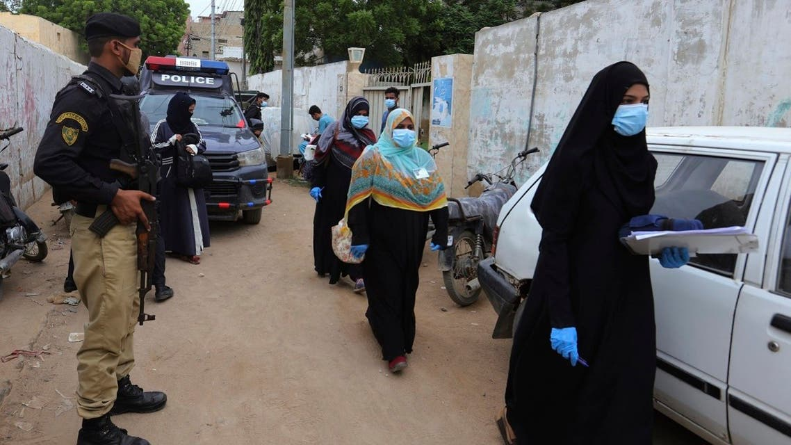 Police officers stand guard while health workers arrive in an area for polio vaccination, in Karachi, Pakistan, Monday, July 20, 2020. (AP)