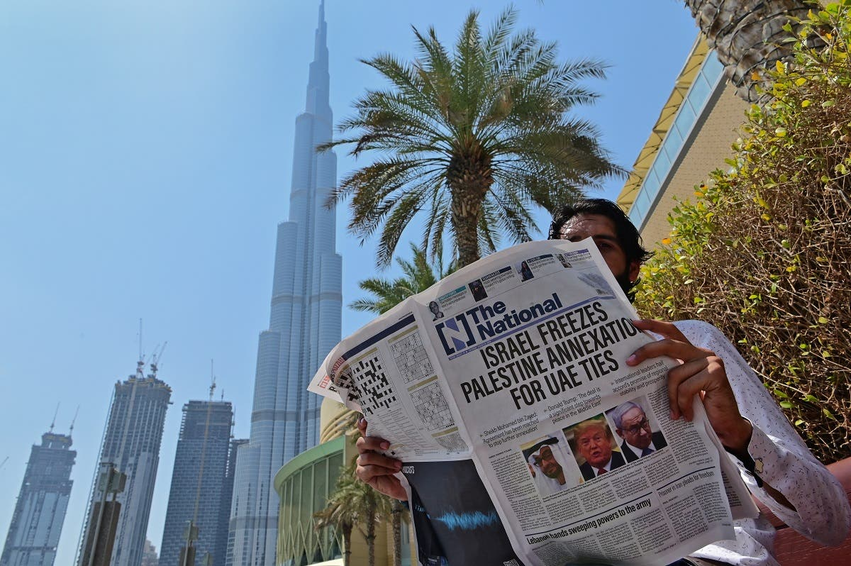 A man reads a copy of UAE-based The National newspaper near the Burj Khalifa, the tallest structure and building in the A man reads a copy of UAE-based The National newspaper near the Burj Khalifa in the gulf emirate of Dubai. (AFP)