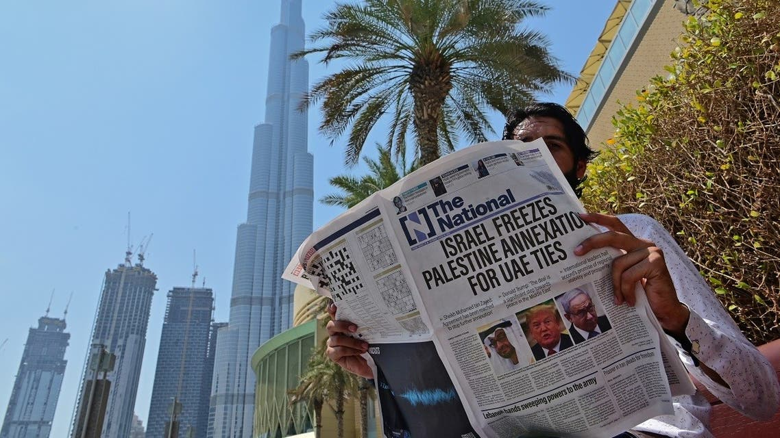 A man reads a copy of UAE-based The National newspaper near the Burj Khalifa, the tallest structure and building in the A man reads a copy of UAE-based The National newspaper near the Burj Khalifa in the gulf emirate of Dubai. (AFP)irate of Dubai