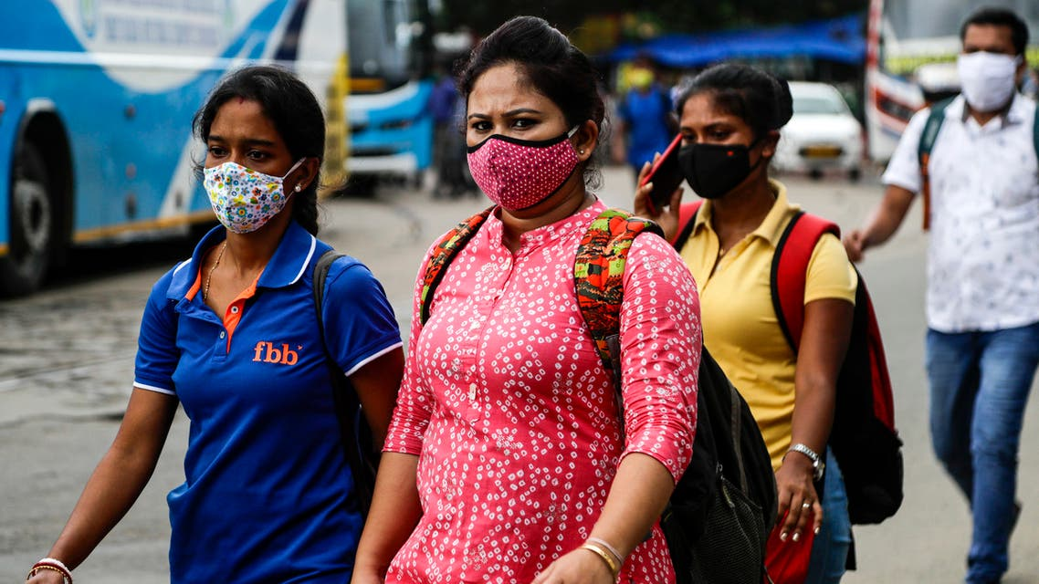 People wearing face masks walk to catch buses in Kolkata, India on Aug. 14, 2020. (AP)