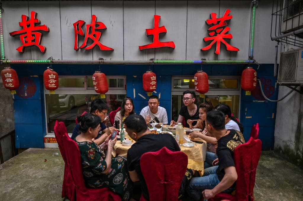 A group of people eat next to a restaurant in Wuhan, China's central Hubei province on May 27, 2020. (File photo: AFP)