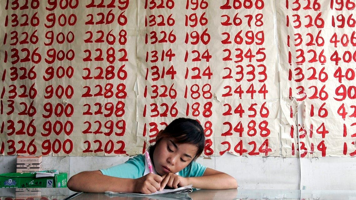 A salesperson waits for customers in front of lists of mobile phone numbers for sale at a shop in Beijing August 11, 2006. (Reuters)