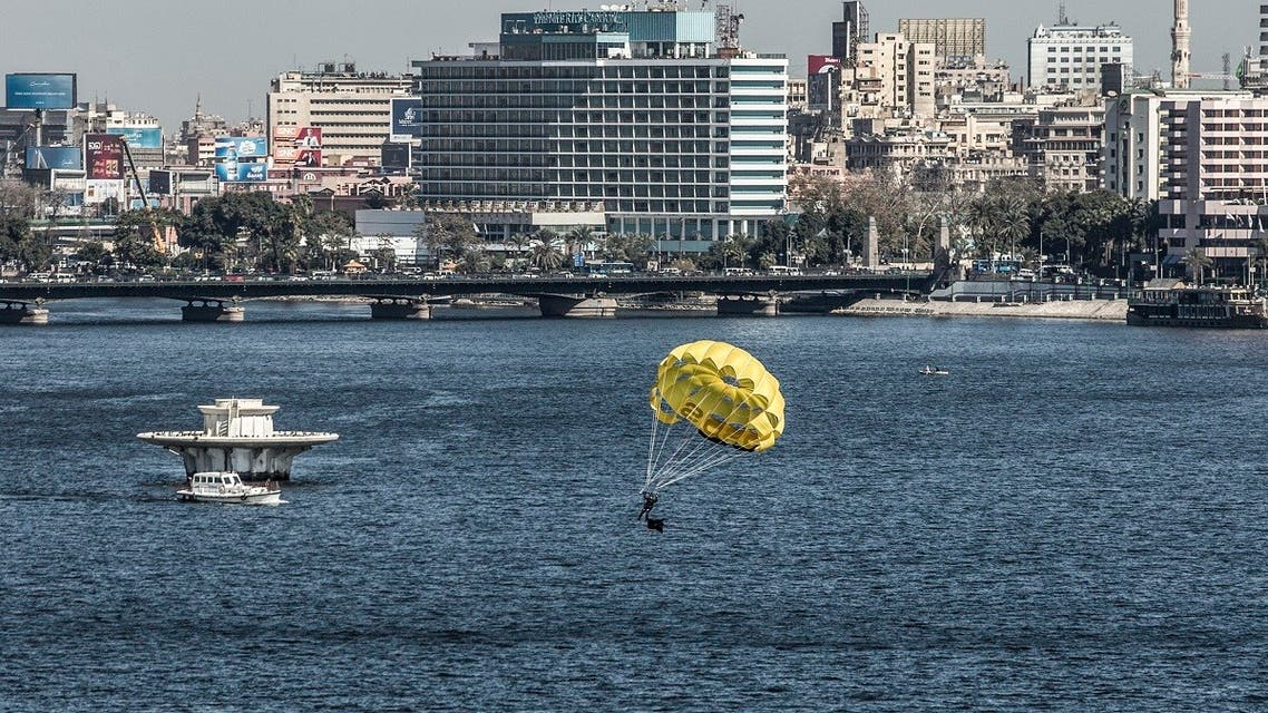 A man parasails in the Nile river during a training session in the Egyptian capital Cairo, on January 26, 2020, with the buildings overlooking the central Tahrir Square seen in the background. (AFP)