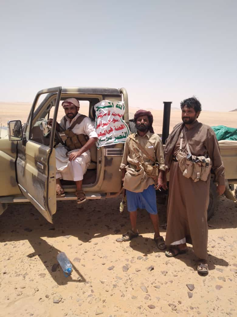 Yemeni army soldiers pictured after a battle against militants and confiscating a Houthi vehicle with the group's slogan still shown on the car. (Supplied)