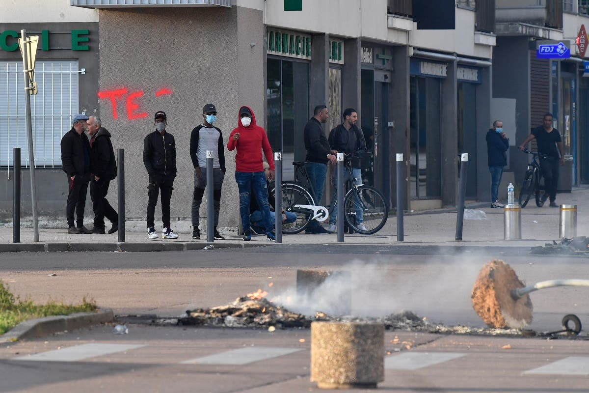 People stand near a torn down street sign and a fire in the street in the Gresilles area of Dijon, eastern France, on June 15, 2020. (AFP)