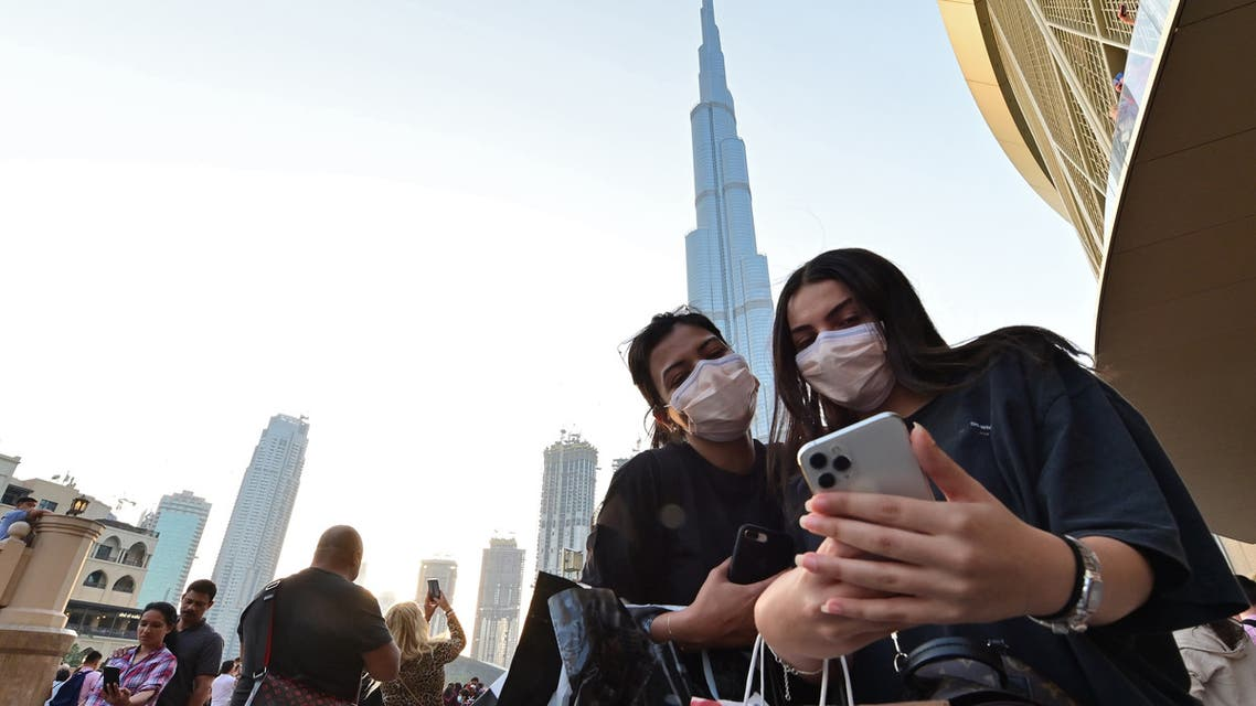 Women wearing protective masks look at a cell phone in front of Burj Khalifa in Dubai on March 8, 2020. (AFP)