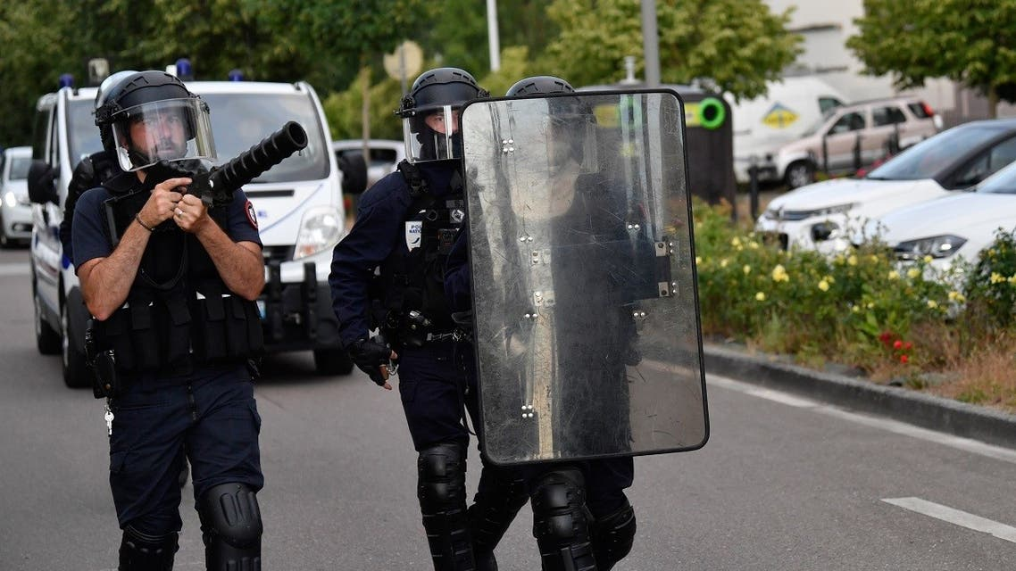 Police walk carrying a shield and a tear gas canister launcher in the Gresilles area of Dijon, eastern France, on June 15, 2020, as new tensions flared in the city after it was rocked by a weekend of unrest blamed on Chechens seeking vengeance for an assault on a teenager. (AFP)