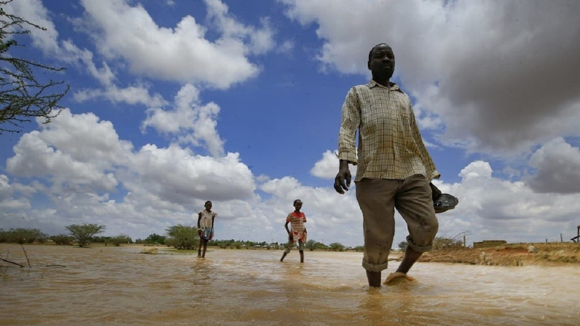 Sudanese men walk in flood water, as a result of flooding and torrential rain, in the town of Osaylat, 50 km southeast of the capital Khartoum, on August 6, 2020. (AFP)