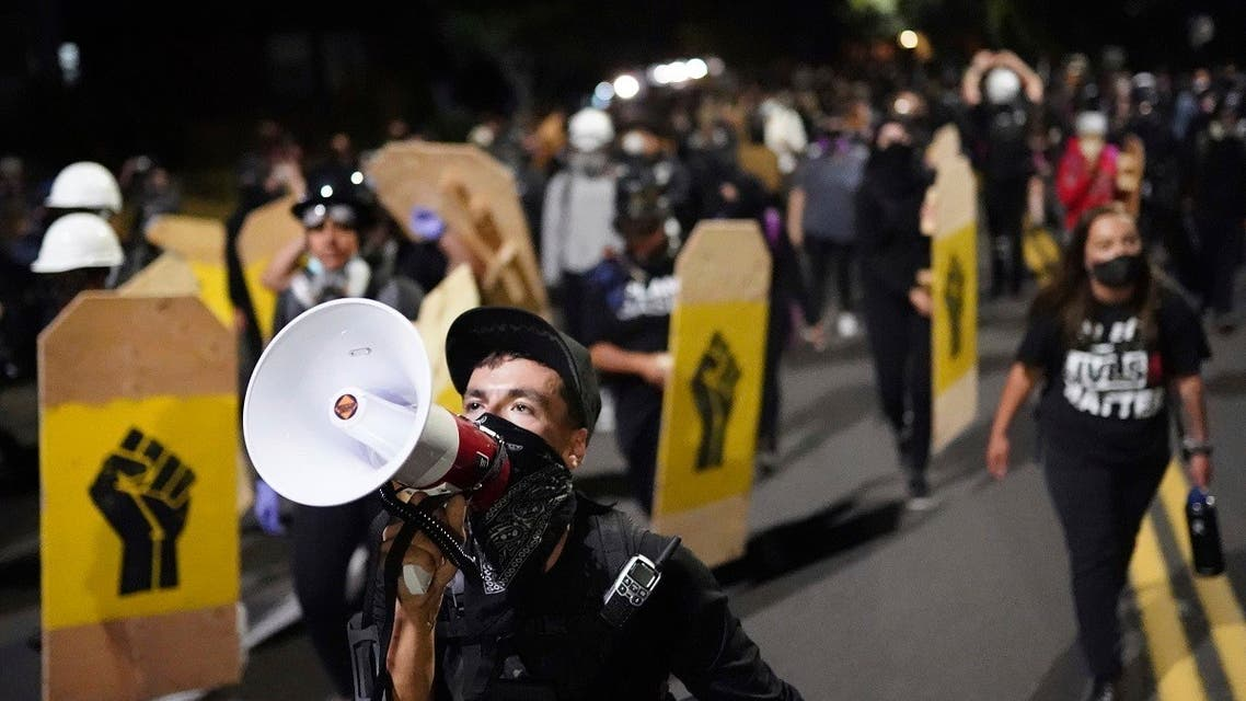 A protester leads a crowd of demonstrators toward the Multnomah County Sheriff's Office on Friday, Aug. 7, 2020 in Portland, Oregon. (AP)