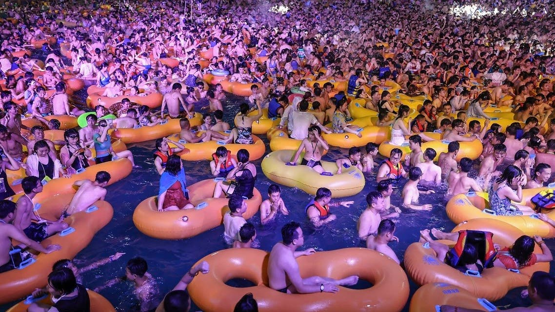 A photo shows people watching a performance as they cool off in a swimming pool in Wuhan in China. (AFP)