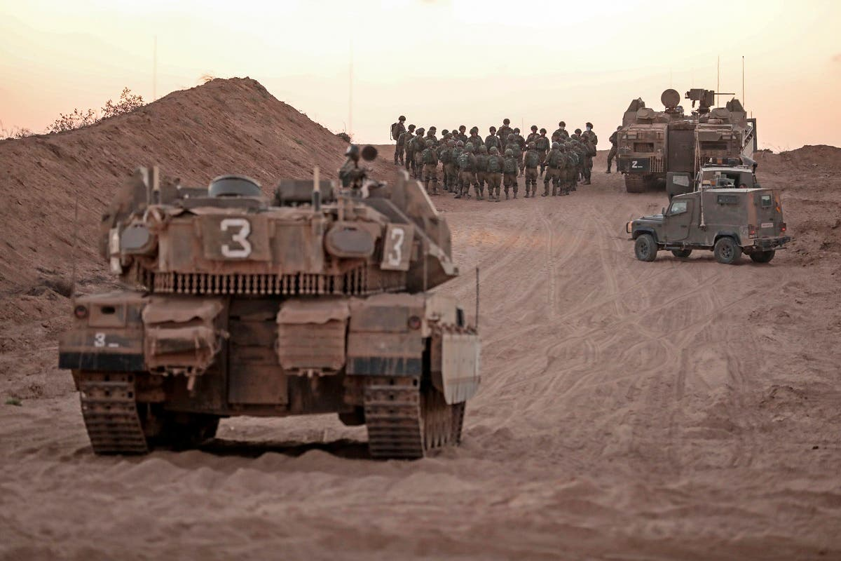Israeli infantry soldiers gather next to tanks and an armoured personnel carrier near the Israeli border with the Gaza Strip, on August 16, 2020. (AFP)
