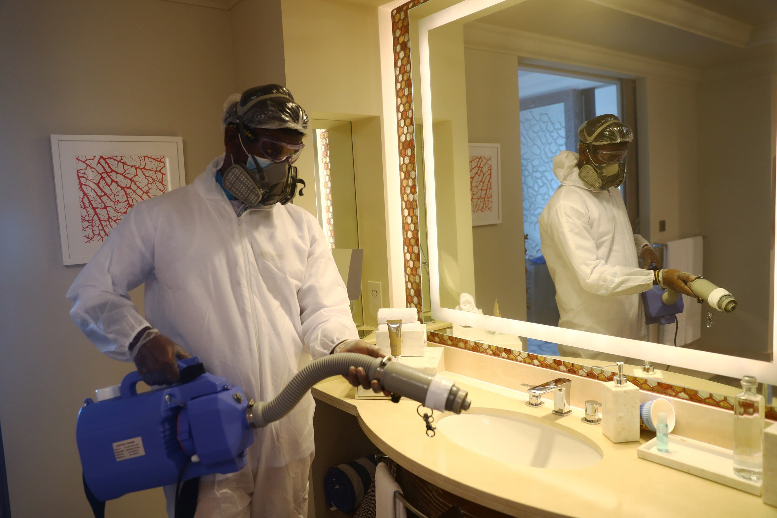 A worker wearing a protective suit sterilizes a bathroom in the Atlantis The Palm hotel in Dubai, United Arab Emirates July 7, 2020. (Reuters)
