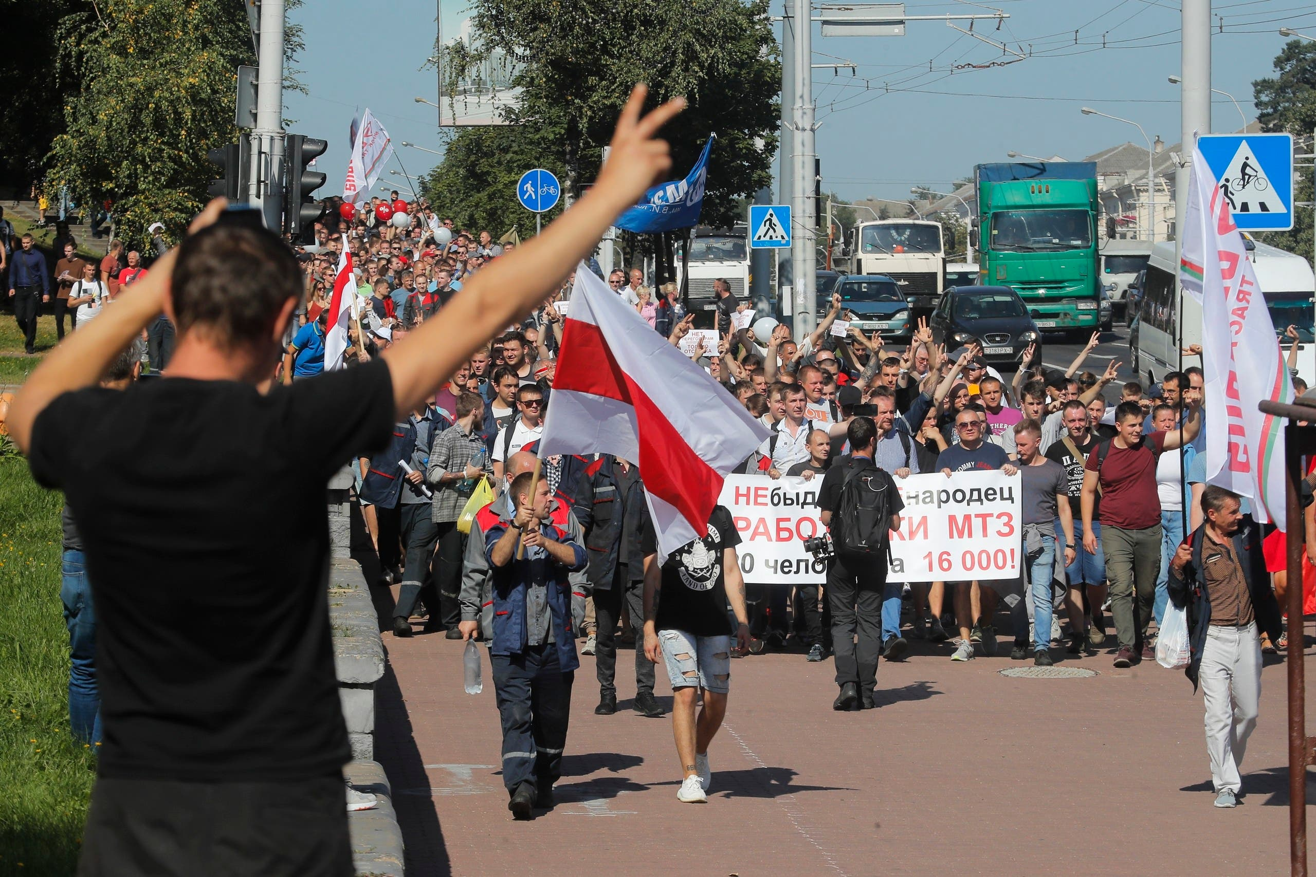 Workers with old Belarusian national flags march toward the Minsk Wheel Tractor Plant where Belarusian President Alexander Lukashenko addresses employees in Minsk, Belarus on Aug. 17, 2020. (AP)