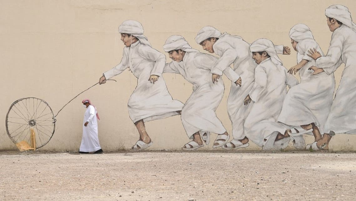 An Emirati man, wearing a protective face-mask, walks past a graffiti in Dubai on March 28, 2020. (AFP)