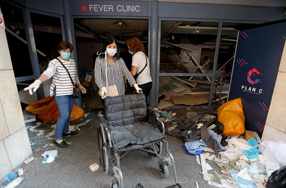 A woman wearing a face mask pushes a wheelchair at a damaged hospital following Tuesday's blast in Beirut Lebanon. (Reuters)