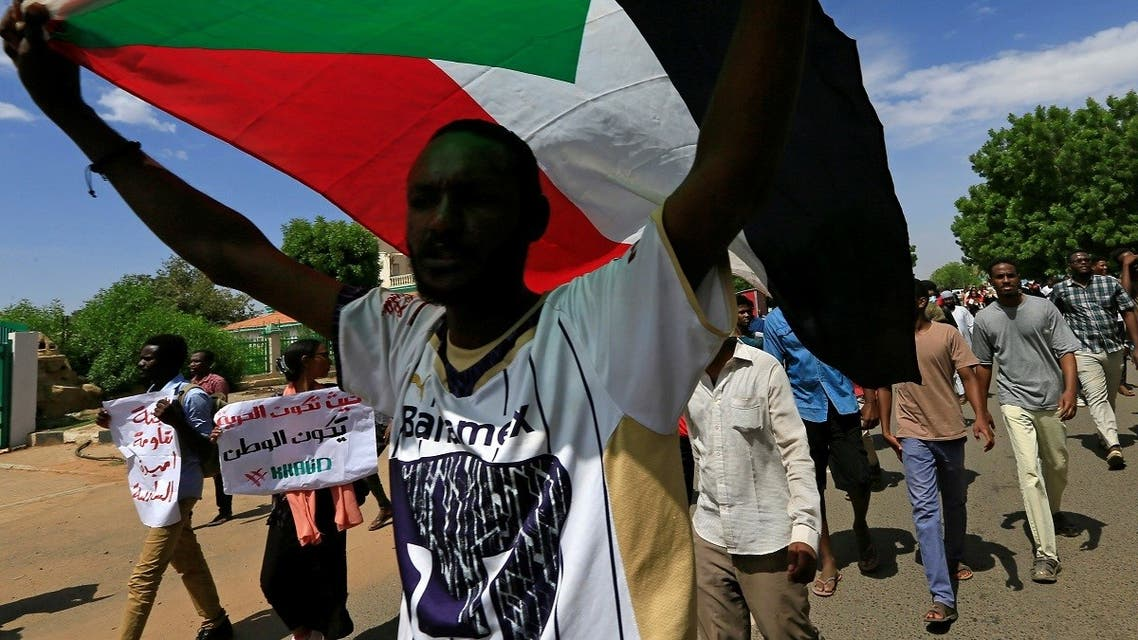 A Sudanese protester carries their national flag as they march in a demonstration to mark the anniversary of a transitional power-sharing deal with demands for quicker political reforms in Khartoum, Sudan, on August 17, 2020. (Reuters)