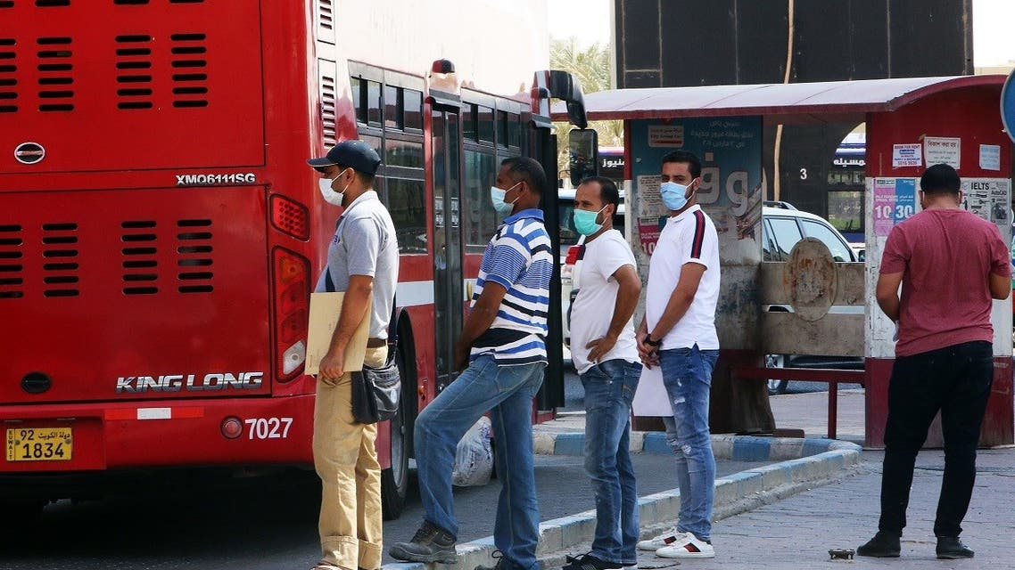 People wearing protective masks wait to board a bus at a station in Kuwait City on August 18, 2020, as businesses reopen after a 5-month shutdown due to the coronavirus. (AFP)