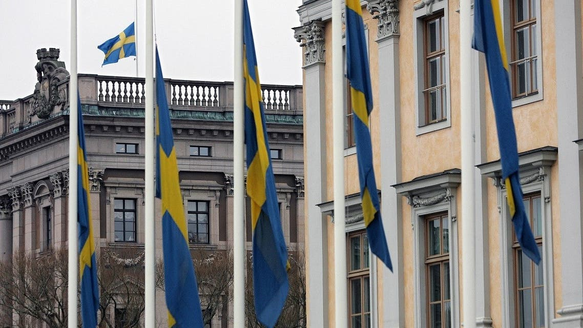 Swedish flags outside the Foreign Ministry and on top of the Riksdag, the parliament building, in Stockholm. (AFP)