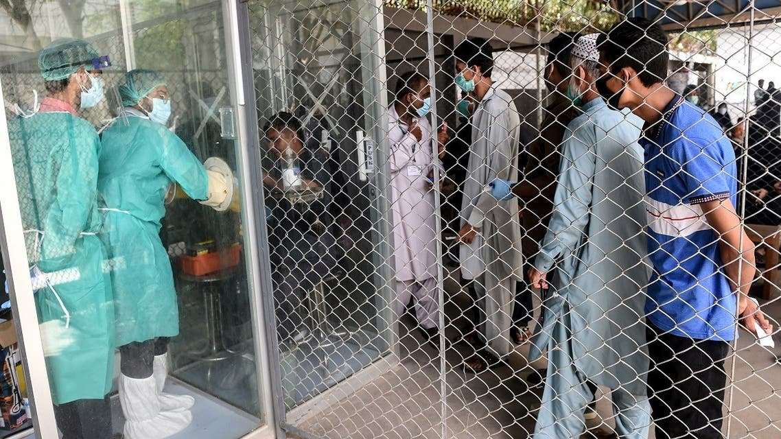 In this picture taken on July 23, 2020, people wait their turn to take a COVID-19 coronavirus test at a testing point in Karachi. (AFP)
