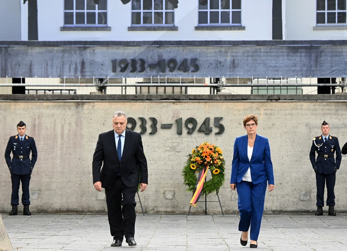 Germany's Defense minister Annegret Kramp-Karrenbauer (R) and Jeremy Issacharoff, Ambassador of Israel in Germany (L), walk together after a wreath laying ceremony in the memorial place concentration camp Dachau near Munich, on August 18, 2020, on the occasion of military exercise. (AFP)