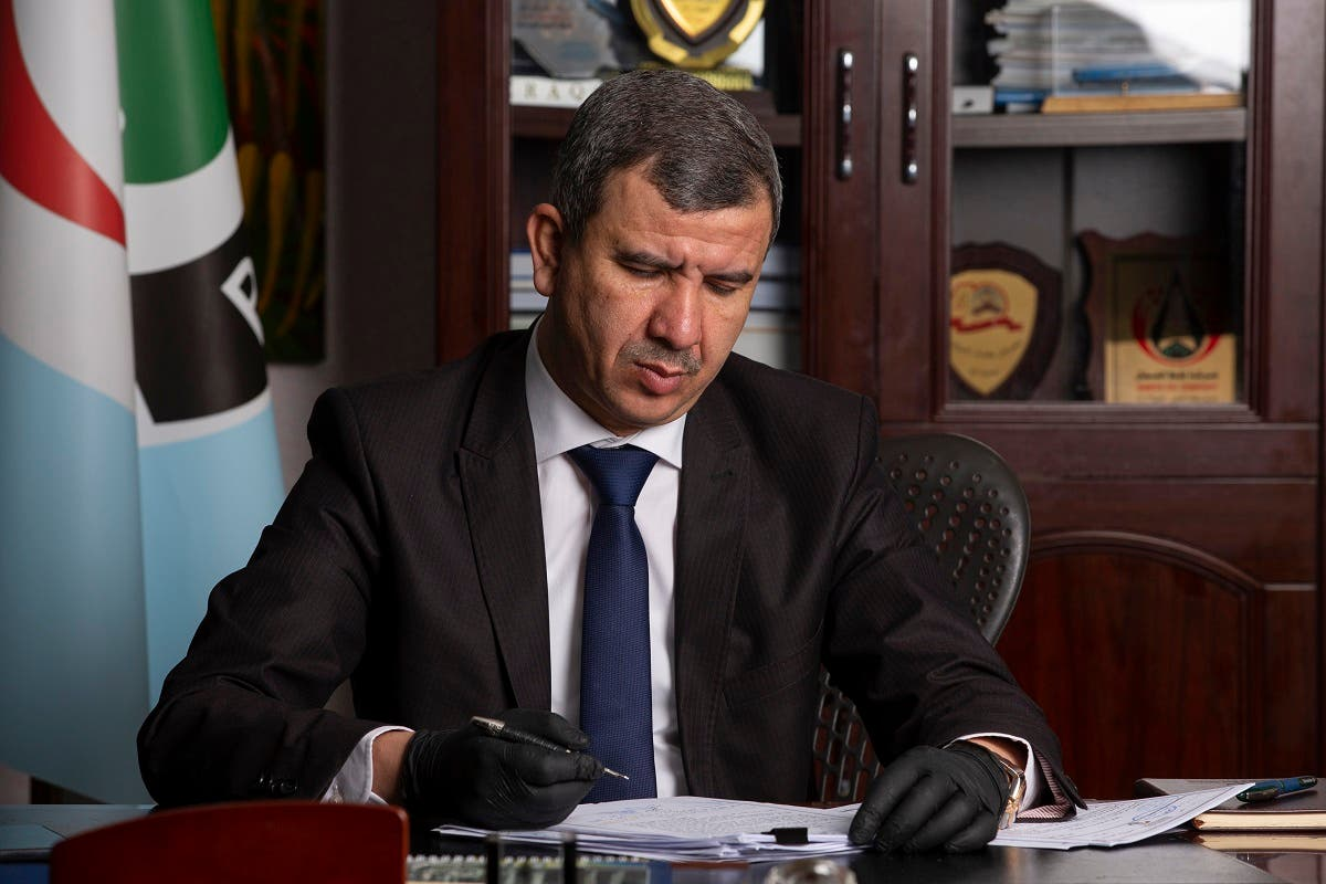 Iraqi Minister of Oil Ihsan Abdul Jabbar reads documents at the Basra Oil Company in Iraq's southern port city, on May 9, 2020. (AFP)