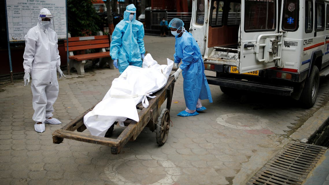 Health workers and relatives wearing personal protective equipment (PPE) carry the body of a man, who died due to the coronavirus disease (COVID-19), for his cremation, at a crematorium in New Delhi, India August 17, 2020. REUTERS/Adnan Abidi
