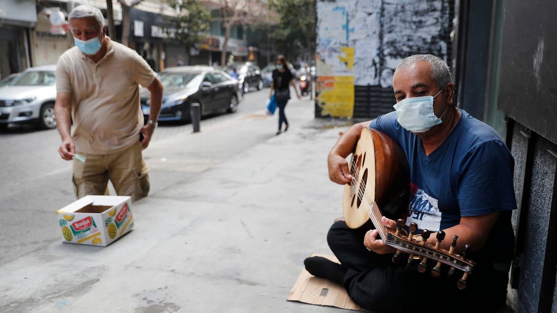 A street musician man performs with a mask on his face to help stop the spread of the coronavirus, as other man on the left puts money on a box, in Beirut, Lebanon on July 29, 2020. (AP)