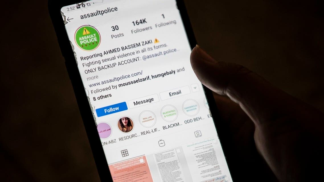 A woman checks on her phone an Instagram account for reporting allegations of sexual harassment and misconduct against Ahmed Bassam Zaki, a 22-year-old student, in Cairo on July 15, 2020. (AFP)