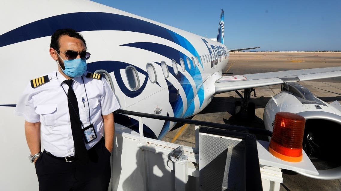A flight attendant wearing a protective face mask stands at the entrance of a plane at Sharm el-Sheikh International Airport. (Reuters)