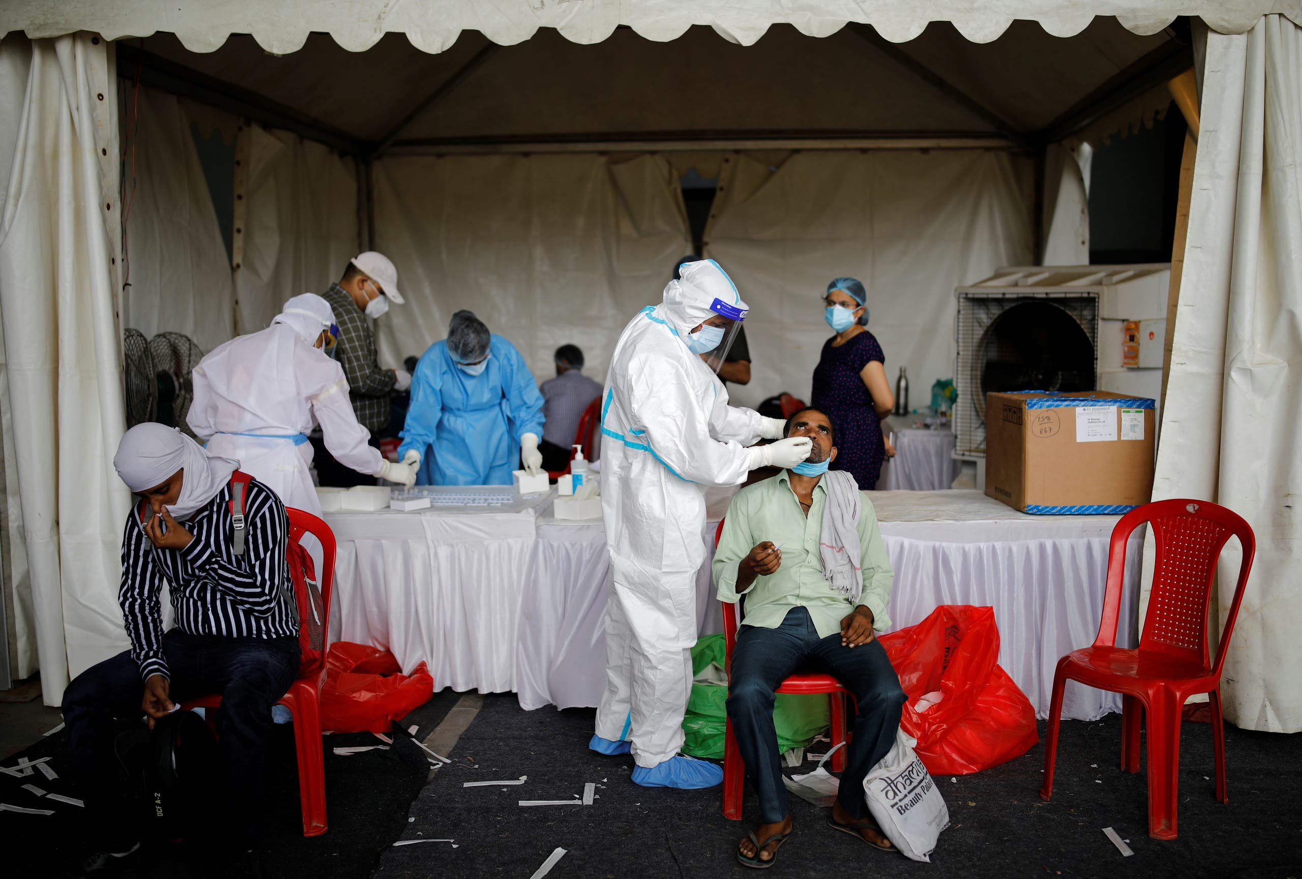 A healthcare worker wearing personal protective equipment (PPE) takes a swab from a migrant worker, who returned to Delhi from his native state, for a rapid antigen test at a bus terminal, amidst the coronavirus disease (COVID-19) outbreak in New Delhi, India, August 17, 2020. (Reuters)