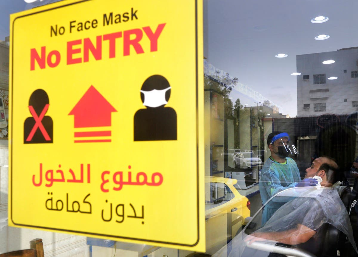 A poster showing healthy procedures to help curb the spread of the coronavirus, hangs at a barber shop window in Jeddah, Saudi Arabia. (AFP)