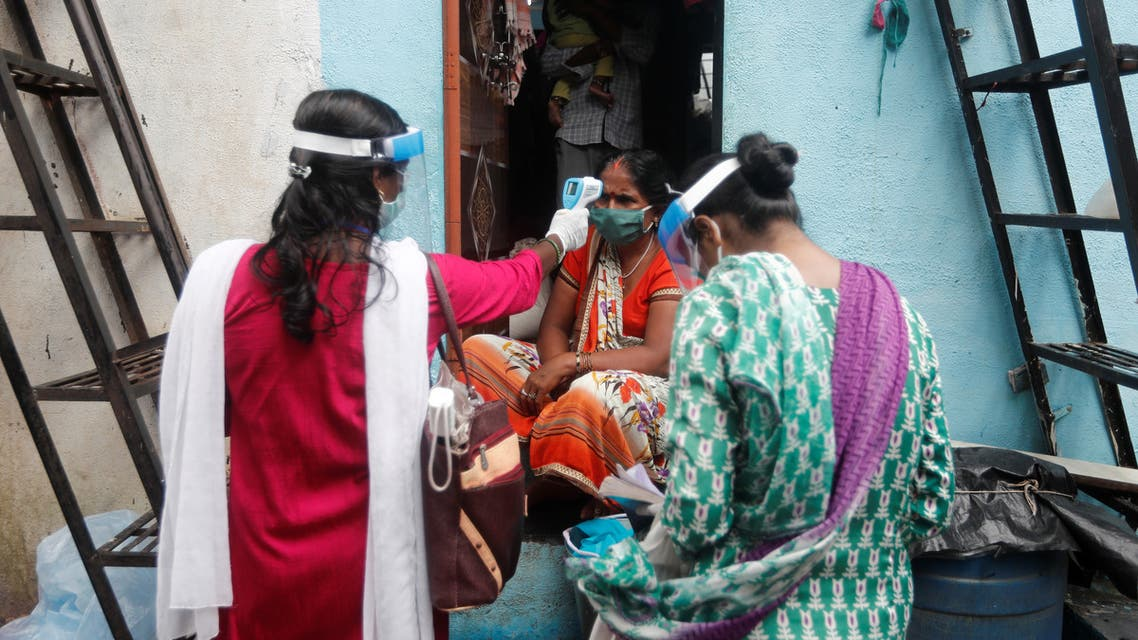 Community health volunteers check the temperature of a woman during a check up campaign for the coronavirus disease (COVID-19), at a slum in Mumbai, India, August 16, 2020. REUTERS/Francis Mascarenhas
