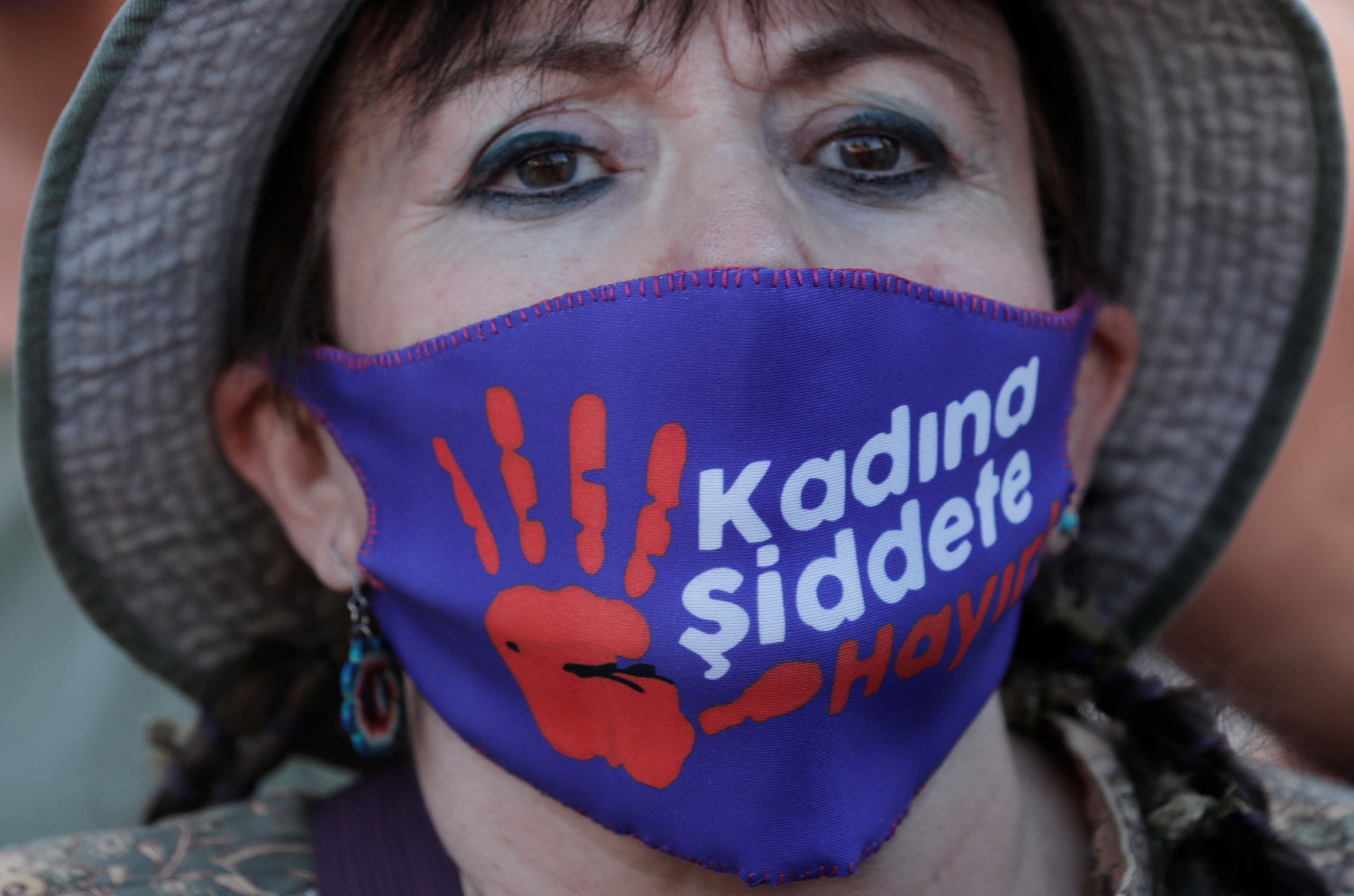 A demonstrator wearing a protective face masks with a sign reading: No to violence against women, takes part in a protest against femicide and domestic violence, amid the coronavirus disease (COVID-19) outbreak, in Istanbul, Turkey August 5, 2020. (Reuters)
