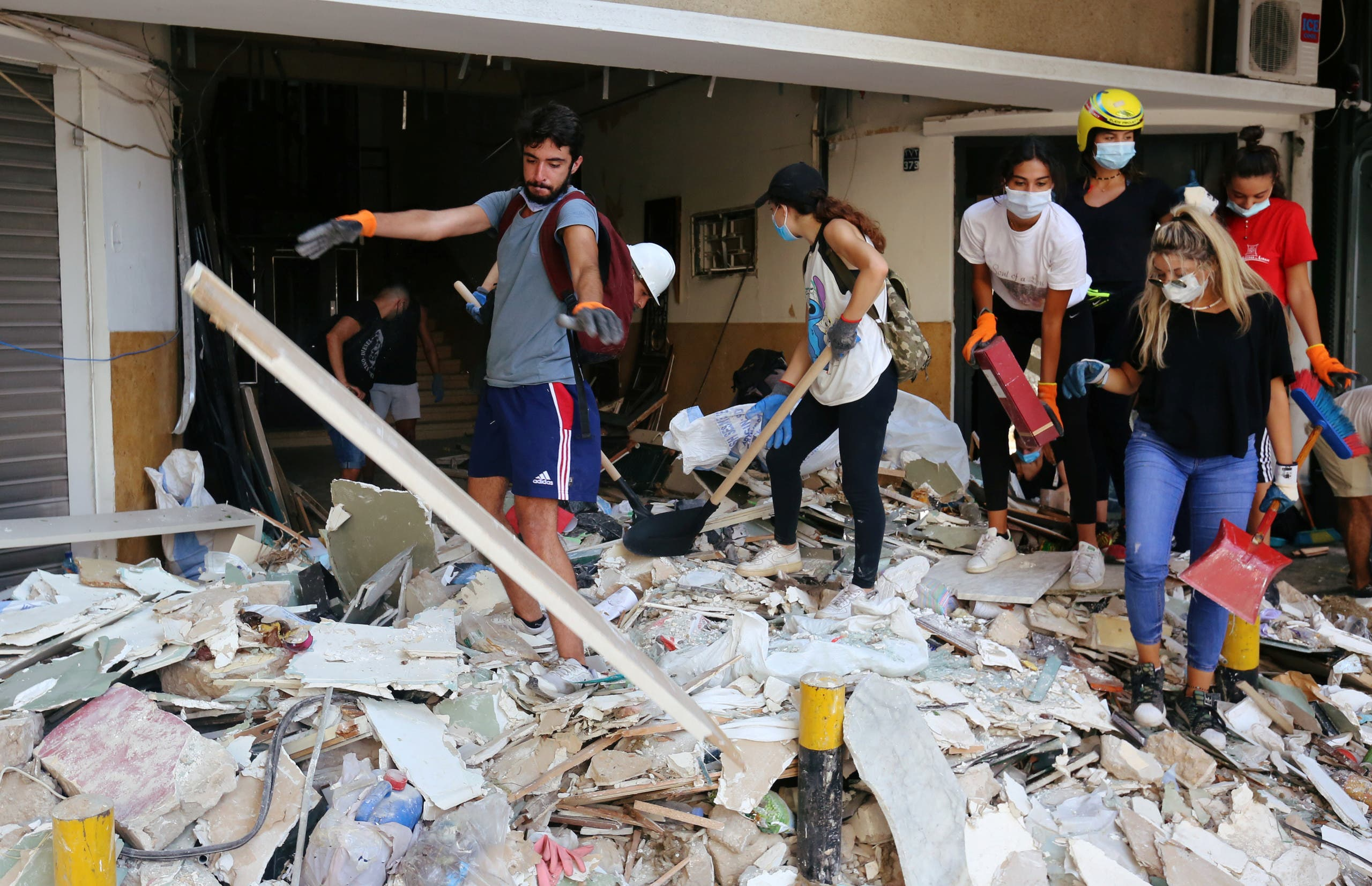 Volunteers clean rubble from the streets following Tuesday's blast in Beirut's port area, in Beirut, Lebanon August 7, 2020. (Reuters)