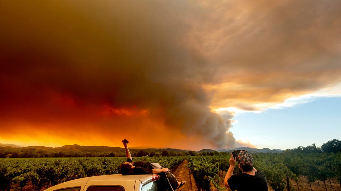 Thomas Henney, left, and Charles Chavira watch a plume spread over Healdsburg, Calif., as the LNU Lightning Complex fires burn on Aug. 20, 2020. (AP)