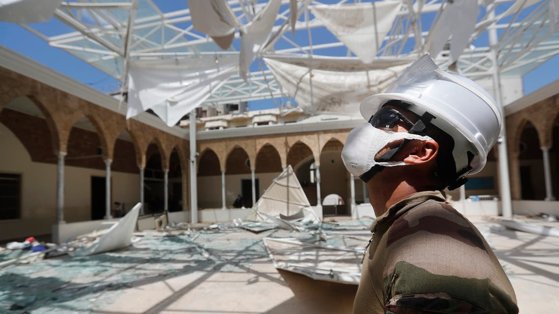 A French soldier looks at his comrades removing the debris of a school playground roof that was destroyed by Aug. 4 explosion that hit the seaport of Beirut on Aug. 20, 2020. (AP)