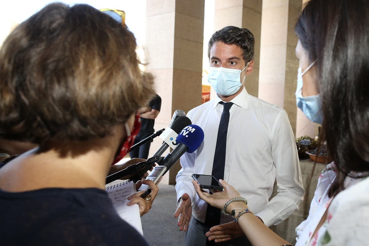 French Secretary of State and Government's spokesperson Gabriel Attal (C) answers journalists' questions at a market in Ajaccio, during a visit to the French Mediterranean island of Corsica on August 12, 2020. (AFP)