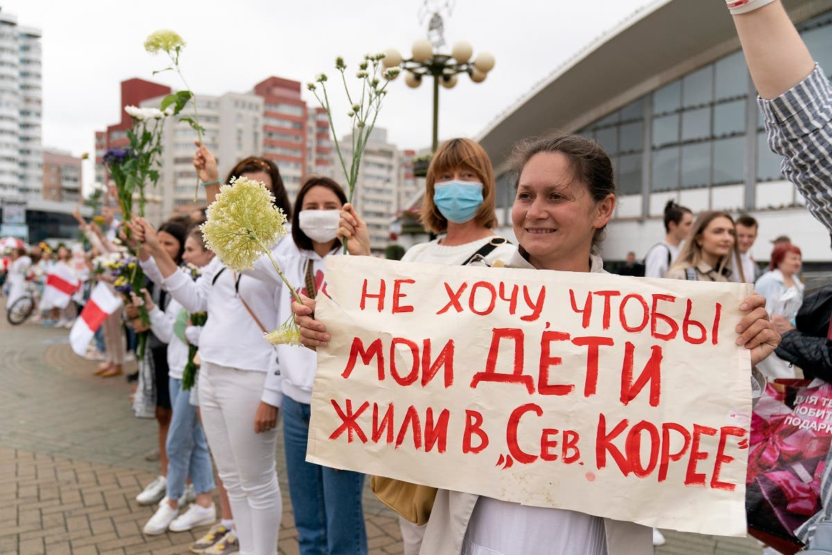 """A woman holds up a poster which reads """"I don't want my children to live in North Korea,"""" during a protest in Minsk, Belarus, August 22, 2020. (AP)"""