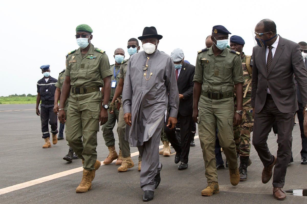Former Nigerian President Goodluck Jonathan (2L) walks at the International Airport in Bamako upon his arrival on August 22, 2020 next to by Malick Diaw (L), the Vice President of the CNSP. (AFP)