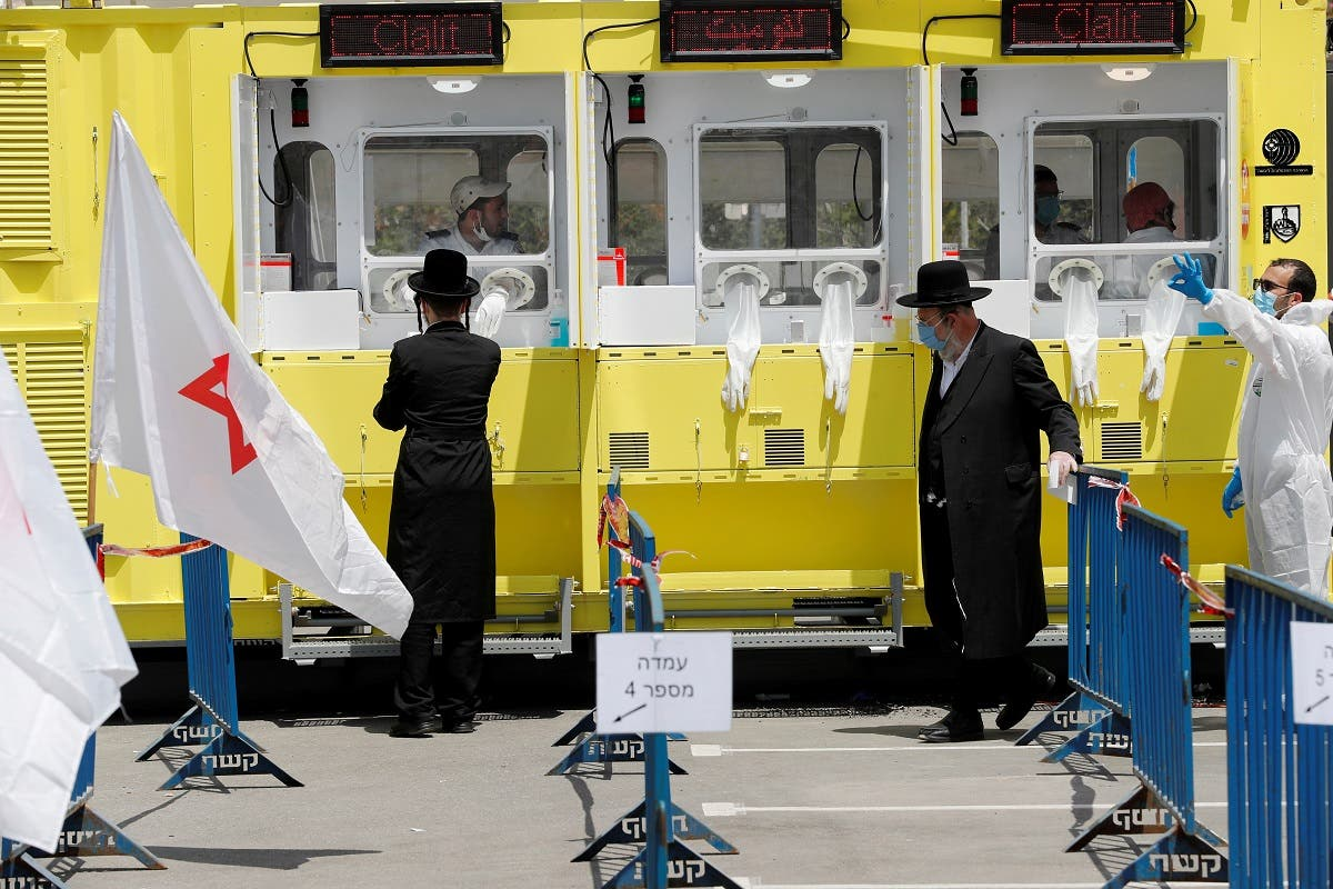 Ultra orthodox Jewish men stand by a testing station for coronavirus disease (COVID-19) in Jerusalem, April 21, 2020. (Reuters)
