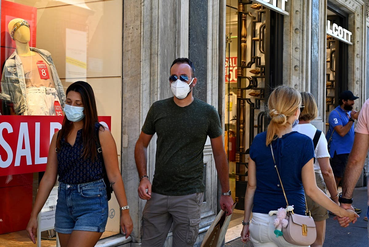 People wearing a face mask walk along the Via del Corso main shopping street on August 20, 2020 in Rome. (AFP)