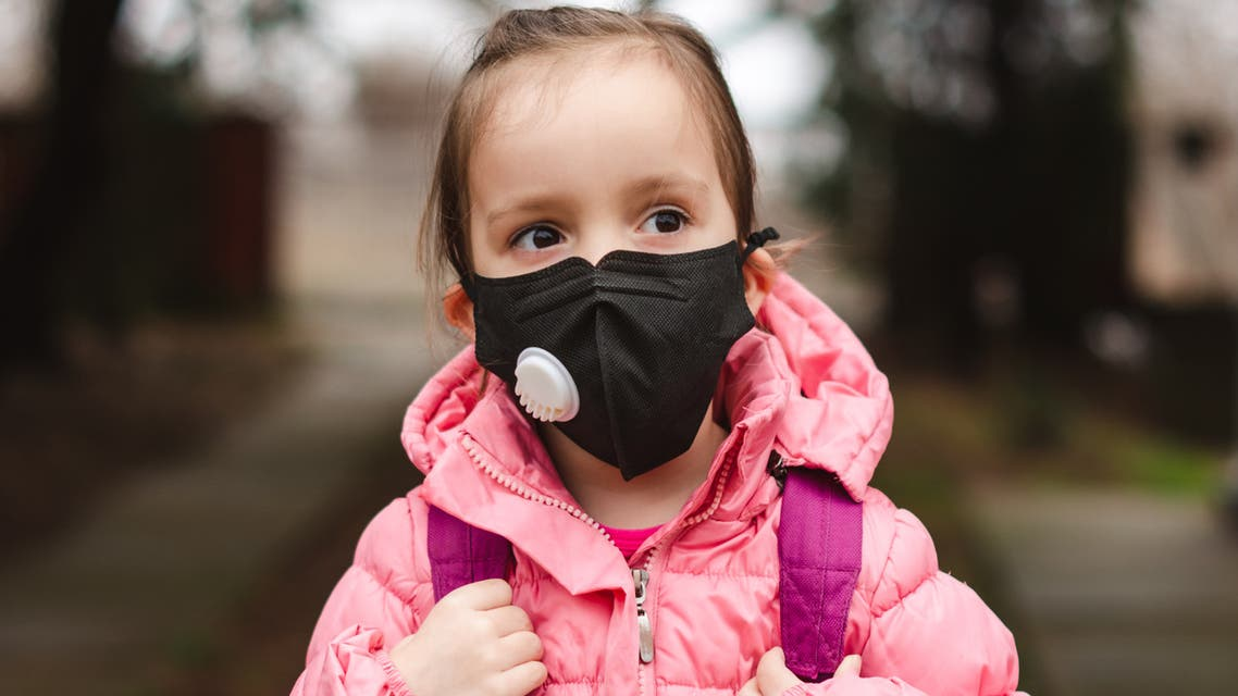 Little girl wearing pollution mask. stock photo