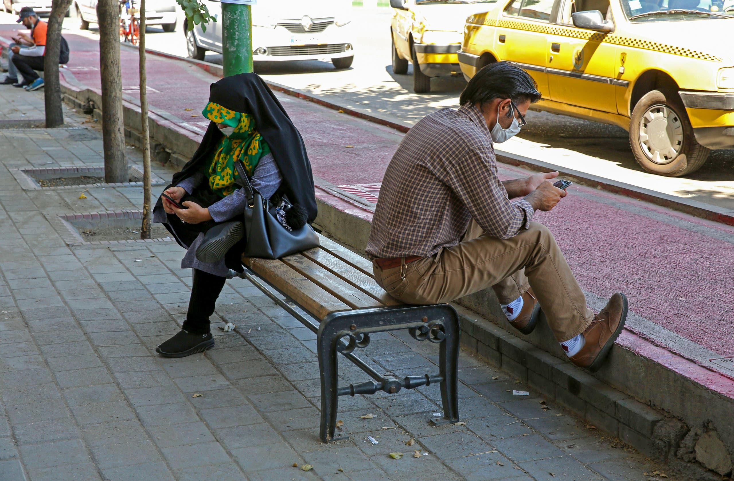 إيرانيان يتفحصان هاتفيهما في طهران في مايو الماضي