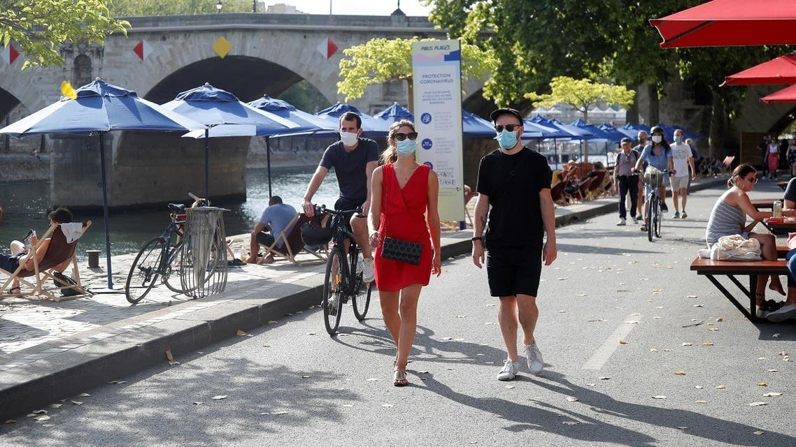 Pedestrians wearing protective face masks walk along the Seine river banks, Paris, France, August 15, 2020. (Reuters)