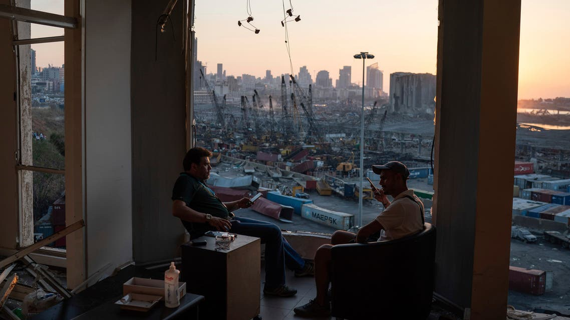 Two men sit on the destroyed balcony of a building facing the site of last week's massive explosion in the port of Beirut, Lebanon, Friday, Aug. 14, 2020. (AP)