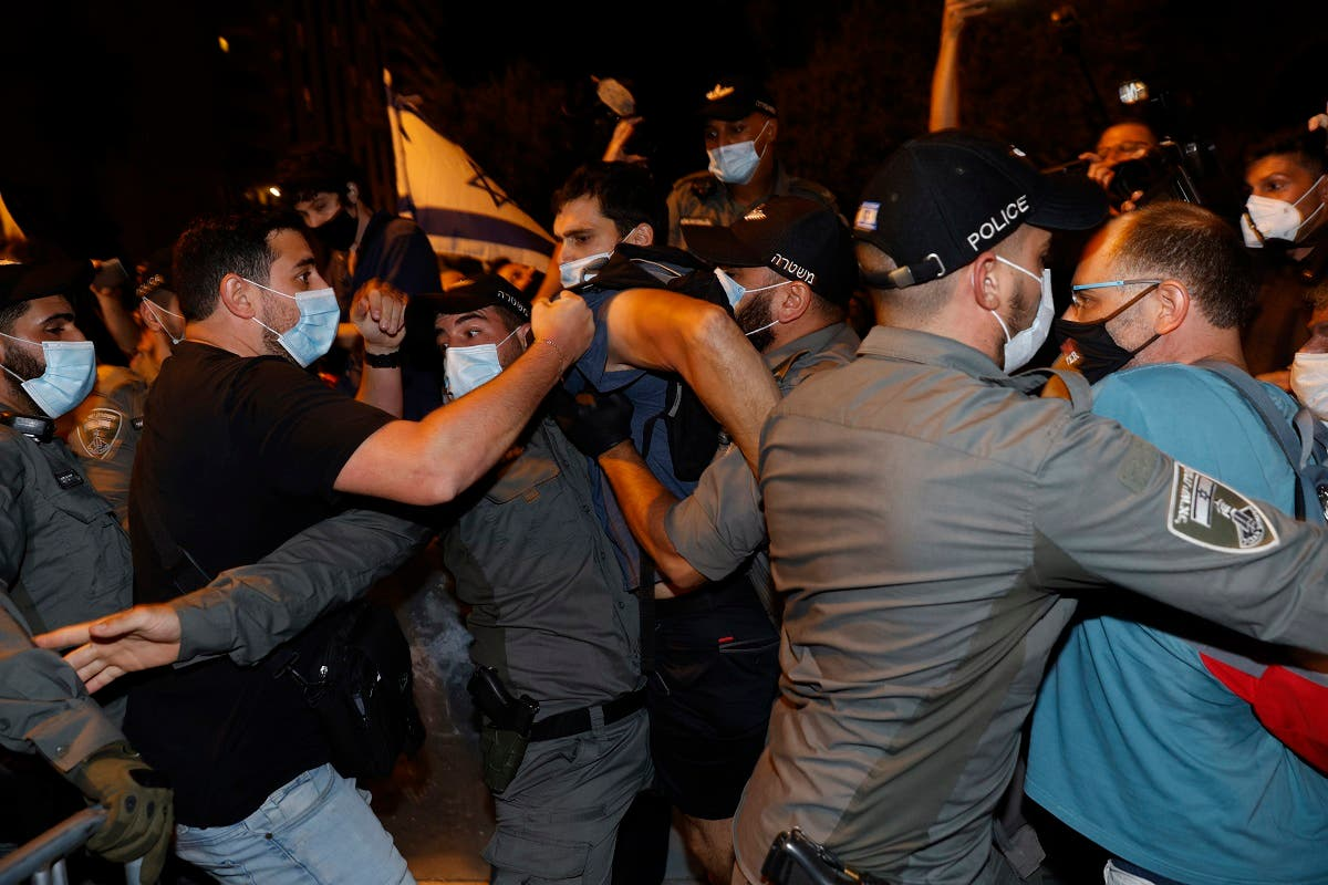 Israeli policemen remove protesters from the street during a demonstration of thousands against the Israeli government near the PM Netanyahu's residence in Jerusalem, August 22, 2020. (AFP)