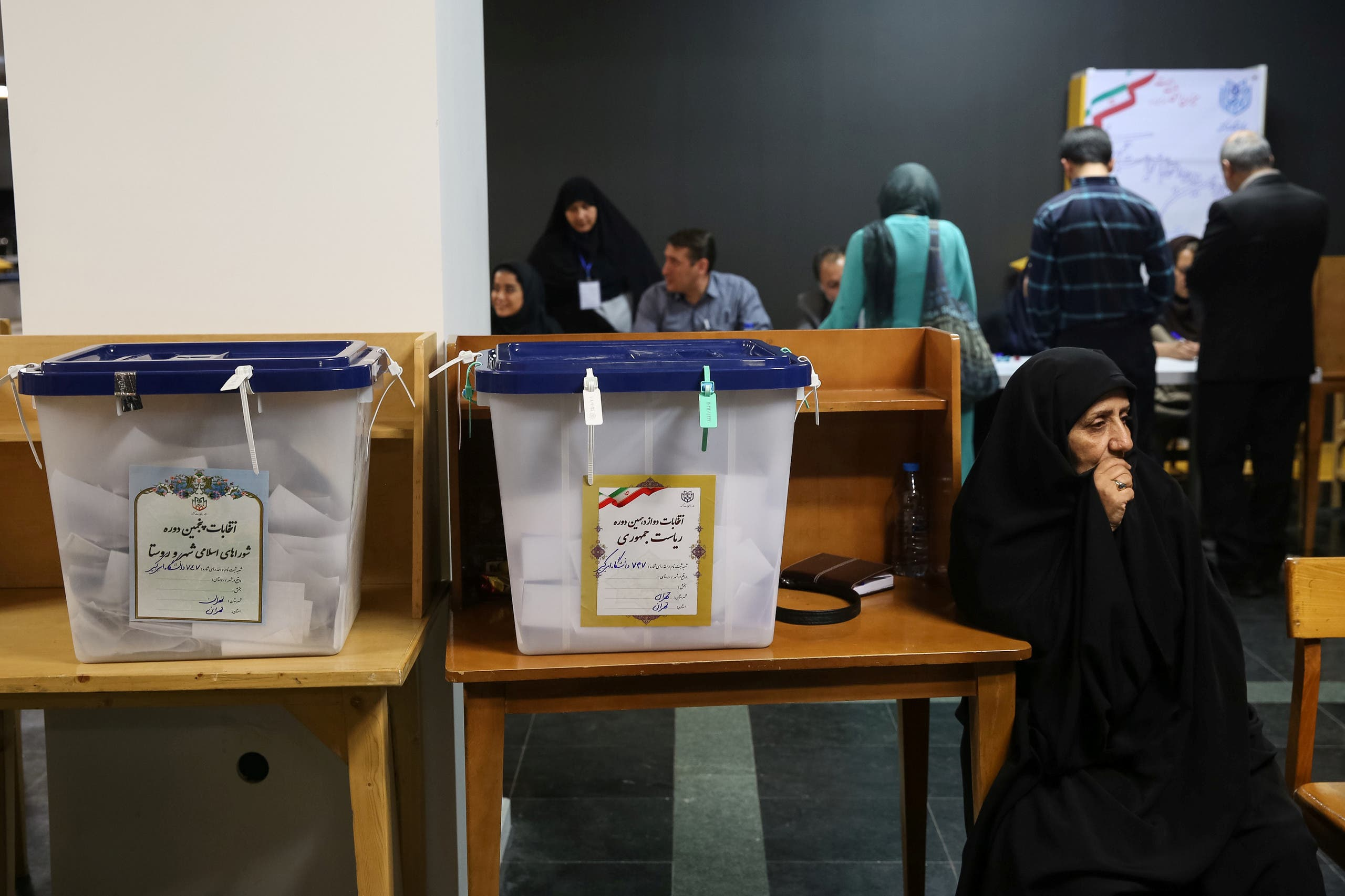 Electoral employees sits next to ballot boxes before closing vote for the presidential election in a polling station in Tehran, Iran, May 19, 2017. (Reuters)