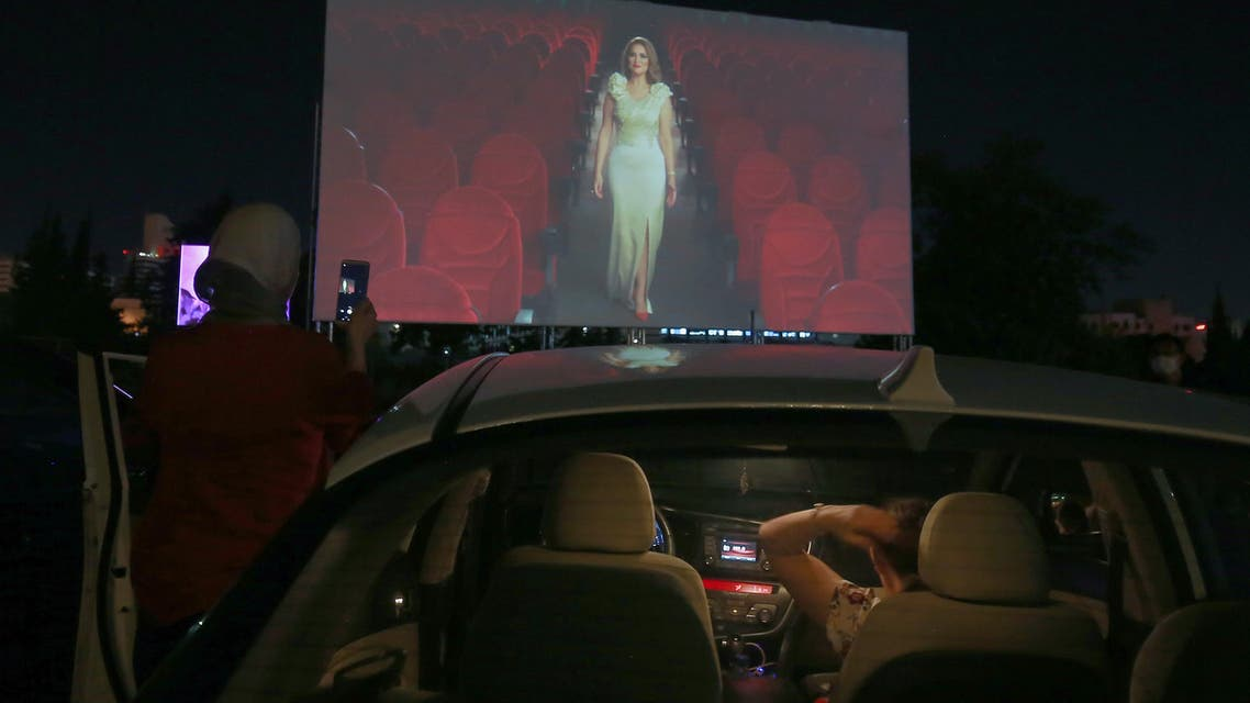 Jordanians sit in their cars at their country's first drive-in cinema, which opened with the French film Les Miserables by Ladj Ly as part of Amman International Film Festival, at a parking lot in New Abdali district in the capital Amman, on August 23, 2020, amid the COVID-19 pandemic.
