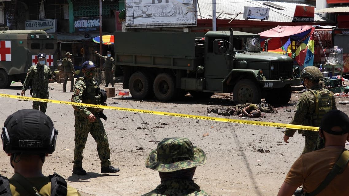 The bodies of victims (C) lie on the pavement as police and military personnel cordon off the site where an improvised bomb exploded next to a military vehicle in the town of Jolo, Sulu province on the southern island of Mindanao on August 24, 2020. At least 10 people were killed and dozens wounded -- many of them soldiers or police -- in a twin bombing on August 24 on a southern Philippine island that is a stronghold of Islamist militants, officials said.